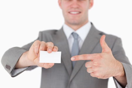 Businessman pointing at a blank business card against a white background photo