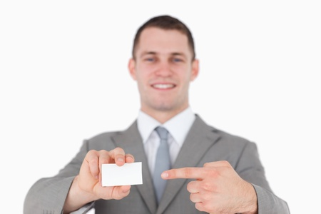 Smiling businessman pointing at a blank business card against a white background photo