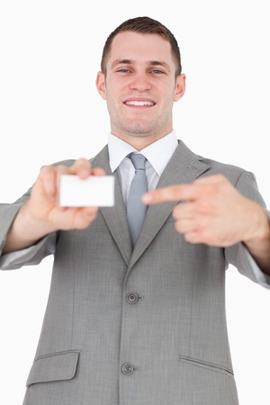Portrait of a businessman pointing at a blank business card against a white background photo