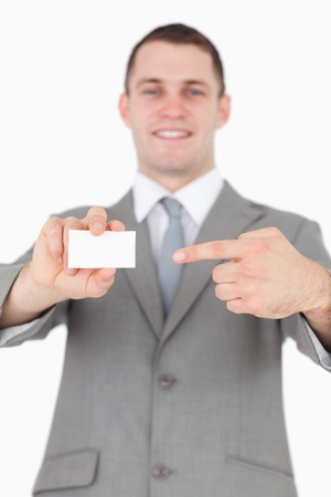 Portrait of a young businessman pointing at a blank business card against a white background photo