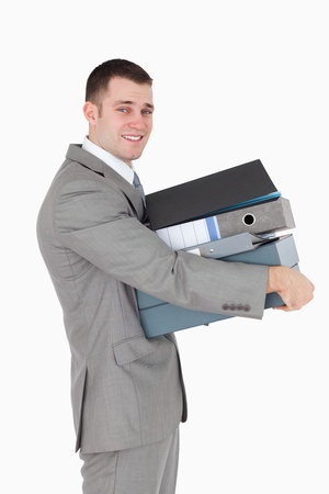 Portrait of a young businessman holding a stack of binders against a white background photo