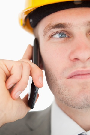 Close up of a young architect making a phone call against a white background photo