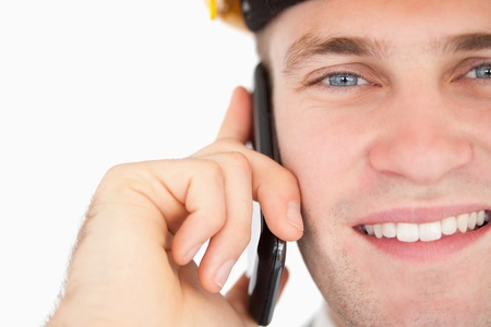 Close up of a handsome architect making a phone call against a white background photo
