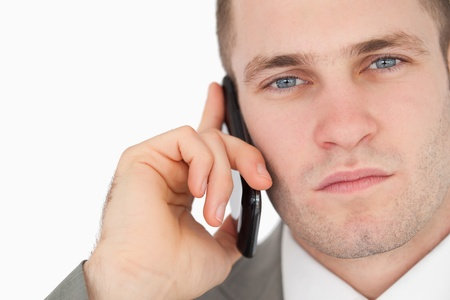 Close up of a focused businessman making a phone call against a white background photo