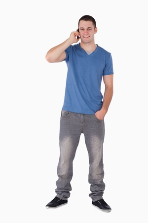 Portrait of a young man making a phone call against a white background photo