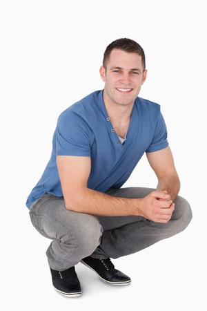squatting: Portrait of a man squatting against a white background Stock Photo