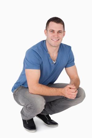 en cuclillas: Retrato de un hombre en cuclillas sobre un fondo blanco