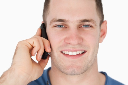 Close up of a smiling man on the phone against a white background photo