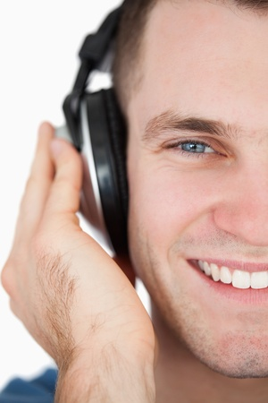 Close up of a smiling man listening to music against a white background photo