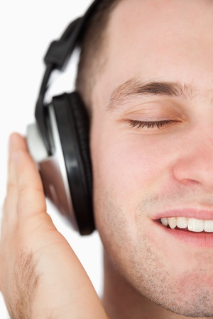 Close up of a serene man listening to music against a white background Stock Photo