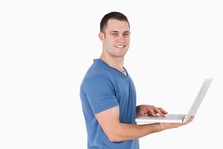 Smiling man using a laptop against a white background Stock Photo