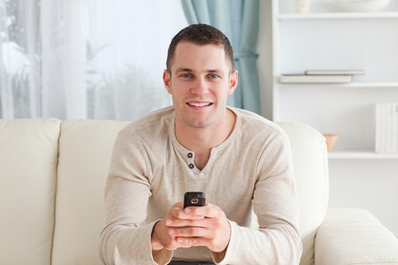 Man sending text messages while sitting on a sofa in his living room photo
