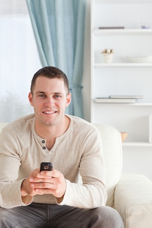Portrait of a man sending text messages while sitting on a sofa in his living room photo