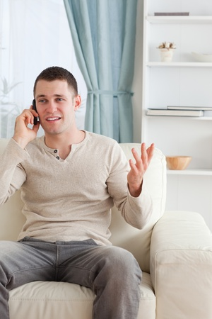 Portrait of a man talking through the phone while sitting on a couch in his living room photo