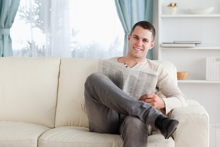 Smiling man reading a newspaper in his living room