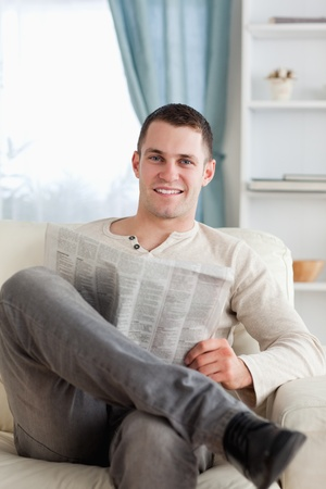 Portrait of a smiling man reading a newspaper in his living room photo