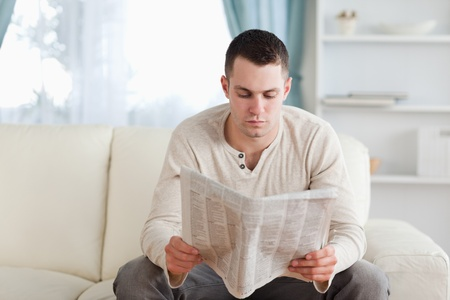 Serious man reading a newspaper in his living room photo