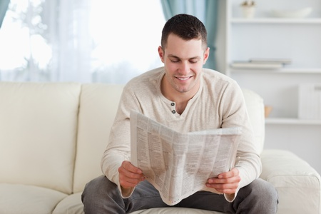 Happy man reading a newspaper in his living room photo