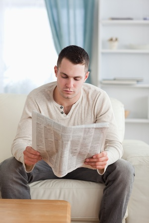 Portrait of a young man reading a newspaper in his living room photo