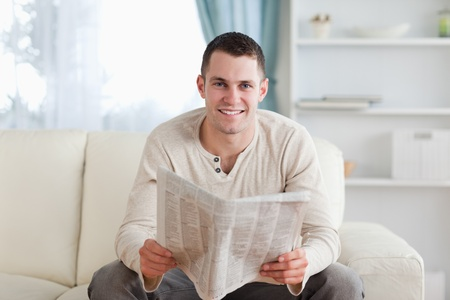 Man holding a newspaper in his living room Stock Photo