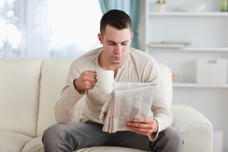 Man reading the news while drinking a coffee in his living room photo