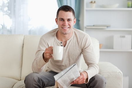 Man holding a newspaper while drinking a tea in his living room photo