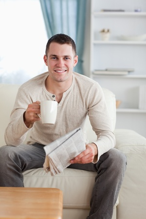 Portrait of a man holding a newspaper while drinking a tea in his living room photo