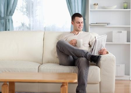Mann mit einem Kaffee beim Lesen der Nachrichten in seinem Wohnzimmer