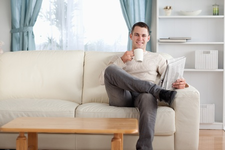Man having a tea while reading the news in his living room photo
