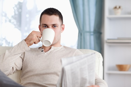 Handsome man having a tea while reading the news in his living room photo