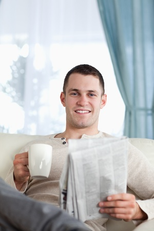 Portrait of a man having a tea while reading the news in his living room photo