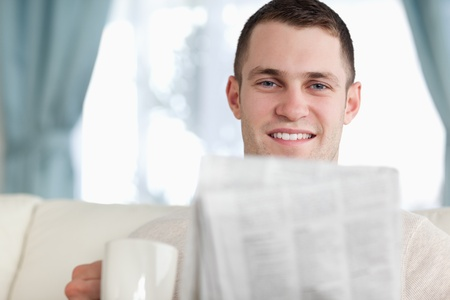 Handsome man having a coffee while reading the news in his living room photo