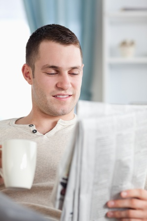Portrait of a smiling man having a coffee while reading the news in living room photo