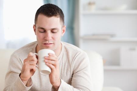 Man having a tea in his living room Stock Photo