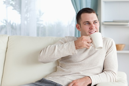 Attractive man having a tea in his living room Stock Photo - 11619976
