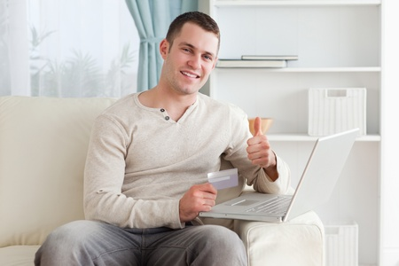 Happy man shopping online with the thumb up in his living room photo