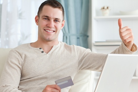 Smiling man shopping online with the thumb up in his living room photo