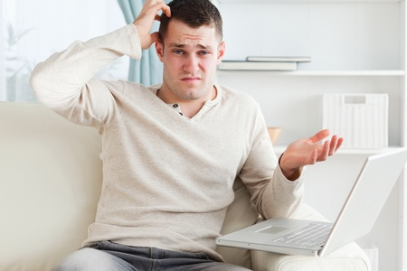 Confused young man using a laptop in his living room photo