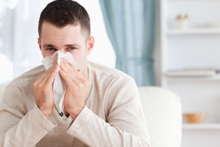 cold virus: Young man blowing his nose in his living room
