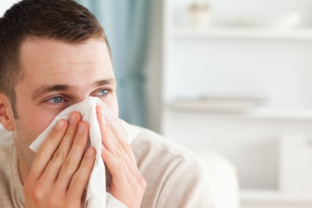 Sick man blowing his nose in his living room photo