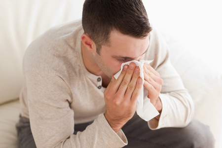 grippe: Ill man blowing his nose in his living room Stock Photo