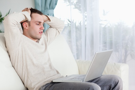 Sad man working with his notebook in his living room photo