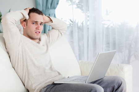 Sad man working with his laptop in his living room photo