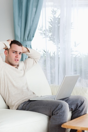 Portrait of a sad man working with his laptop in his living room photo