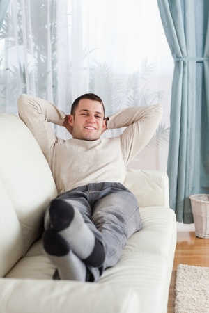 Portrait of man lying on a sofa in his living room photo