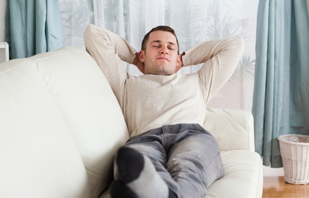 Young man resting on a sofa in his living room photo