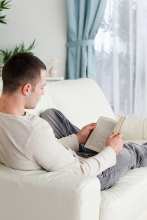 Portrait of a man lying on a sofa reading a book in his living room