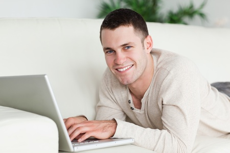 Man lying on a sofa with a laptop while looking at the camera Stock Photo