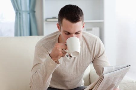 Young man reading the news while having a coffee in his living room photo