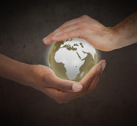 Hands protecting a glowing planet globe against a white background photo